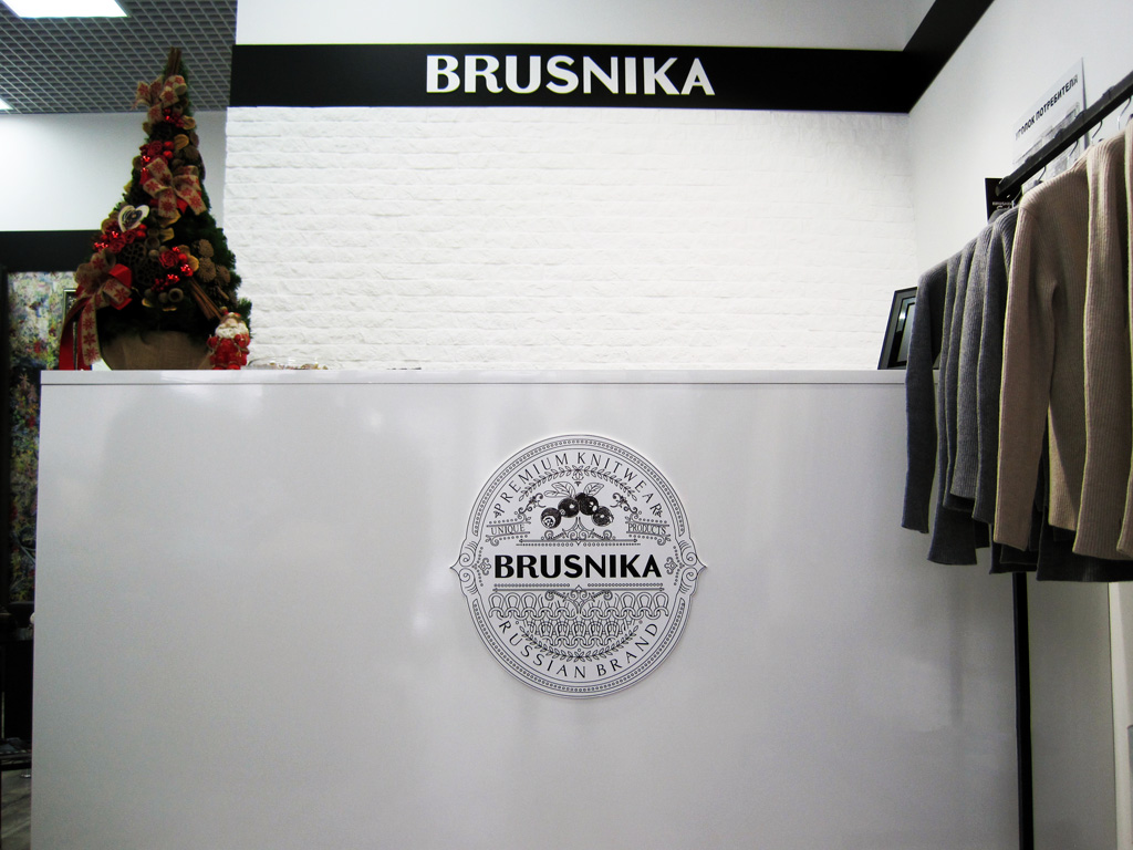 Магазин «Brusnika», несветовой логотип на стойке ресепшена